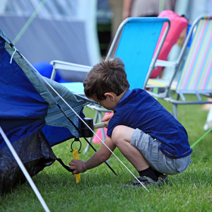 A boy pitching up his tent at Long Meadow Campsite